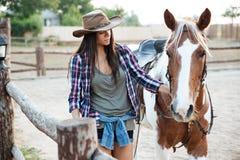 Cow-girl de femme marchant avec son cheval sur le ranch Image stock