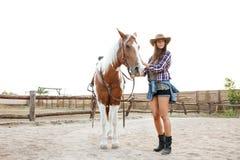 Cow-girl de jeune femme marchant avec son cheval dans une ferme Photos stock