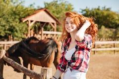 Cow-girl de sourire de femme avec le cheval se reposant sur le ranch Photos libres de droits
