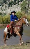 Cow-girl et cheval apparaissant de l'étang Photographie stock libre de droits