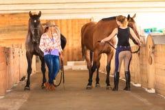 Cow-girl et jockey marchant avec des chevaux dans l'écurie Photo stock