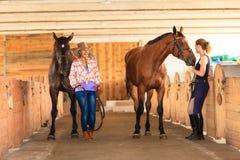 Cow-girl et jockey marchant avec des chevaux dans l'écurie Photo libre de droits
