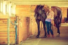 Cow-girl et jockey marchant avec des chevaux dans l'écurie Images stock