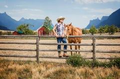 Cow-girl et son cheval se tenant prêt une barrière en bois Image stock