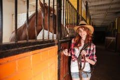 Cow-girl gaie de femme avec le cheval se tenant dans l'écurie Photo libre de droits