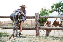 Cow-girl gaie de femme dans la selle de participation de chapeau pour le cheval d'équitation Photo libre de droits