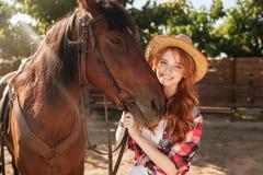 Cow-girl gaie de femme dans le chapeau avec son cheval dans le village Photo libre de droits