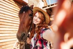 Cow-girl gaie de femme se tenant prenante le selfie avec le cheval à la ferme Photos libres de droits