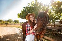 Cow-girl gaie de jeune femme se tenant avec son cheval dans le village Images stock