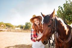 Cow-girl gaie de jeune femme se tenant avec son cheval dans le village Image stock
