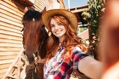 Cow-girl heureuse de femme prenant le selfie avec son cheval sur le ranch Photo stock