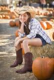 Cow-girl mignonne dans le chapeau et bottes à la correction de potiron Photographie stock libre de droits