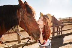 Cow-girl mignonne de femme tenant et embrassant son cheval Photos libres de droits