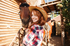 Cow-girl mignonne gaie de jeune femme dans le chapeau avec le cheval Images stock