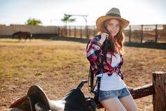 Cow-girl rousse mignonne s'asseyant et se reposant sur la barrière de ranch Images stock