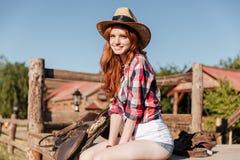 Cow-girl rousse mignonne s'asseyant et se reposant sur la barrière de ranch Photos libres de droits