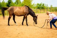 Cow-girl se tenant à côté de l'ami brun de cheval Image libre de droits