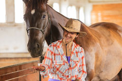 Cow-girl se tenant à côté de l'ami brun de cheval Images libres de droits