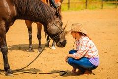 Cow-girl se tenant à côté de l'ami brun de cheval Photos libres de droits