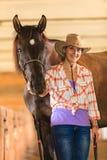 Cow-girl se tenant à côté de l'ami brun de cheval Photographie stock libre de droits
