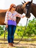 Cow-girl se tenant à côté de l'ami brun de cheval Images stock