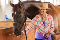 Cow-girl se tenant à côté de l'ami brun de cheval Image stock