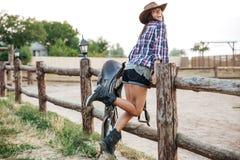 Cow-girl se tenant à la barrière de ranch Image stock