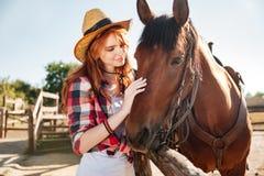 Cow-girl tendre de sourire de jeune femme avec son cheval sur le ranch Photo libre de droits