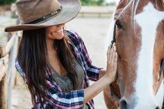 Cow-girl tendre de sourire de jeune femme dans le chapeau avec son cheval Photos libres de droits