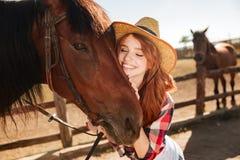 Cow-girl tendre heureuse de jeune femme étreignant son cheval Images stock