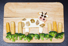 Cow with landscape made from cheese, white carrots, broccoli, mushroom and ham, artistic food concept Royalty Free Stock Image