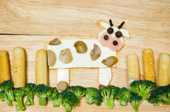 Cow with landscape made from cheese, white carrots, broccoli, mushroom and ham, artistic food concept Stock Photography