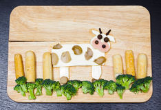 Cow with landscape made from cheese, white carrots, broccoli, mushroom and ham, artistic food concept Royalty Free Stock Images