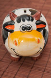 Cow piggy bank. On a wooden background Royalty Free Stock Photos