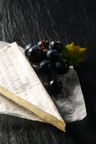 Cow's Milk Cheese Wedge and Grapes on a Paper Stock Photography