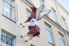 Cow sculpture on the wall of the house. Near an open window royalty free stock image