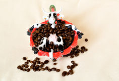Red coffee cup with coffee beans and toy cow - coffee with milk Stock Image
