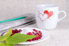 Cowberry in sugar against a mug with hearts Royalty Free Stock Images