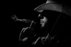 Cowboy. A cowboy blow  off smoke from his hand-gun Royalty Free Stock Photos