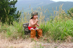 Cowboy. Young boy in father's boots Royalty Free Stock Image