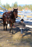 Cowboy. Young boy leading his horse in the riding pen Royalty Free Stock Images