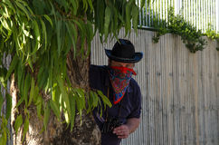 Cowboy ambushing in bandana behind eucalyptus Stock Photos