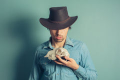 Cowboy with animal skull. A young cowboy is holding an animal skull Stock Photos