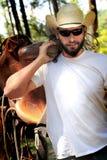 Cowboy avec la selle photographie stock