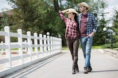 Cowboy avec son amie marchant sur la voie en parc à la journée Photo libre de droits