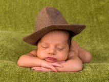 Cowboy baby. Adorable African newborn baby of 7 days old sleeping on a green blanket Royalty Free Stock Photography