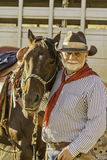 Cowboy barbu blanc par son cheval photographie stock