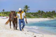 Cowboy On A Beach. A cowboy walking a horse on a caribbean beach royalty free stock photos