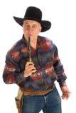 Cowboy blowing top of gun. Stock Images
