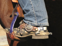 Cowboy boot in saddle stirrup. Close-up of a cowboy boot with spur in the saddle stirrup on a horse stock photography